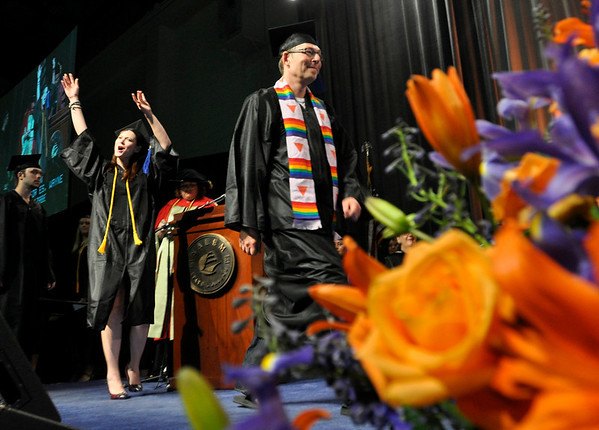 Salem: Rebecca Gustison, left, celebrates while she walks across the stage with Wayne Godfrey as they receive their diplomas for a B.S. in Psychology. photo by Mark Teiwes / Salem News