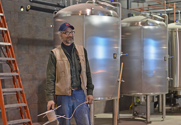 Ipswich:  Conractor Jim Cram of Danvers puts the finishing touches on the installation of the distillery.   photo by Mark Teiwes / Salem News