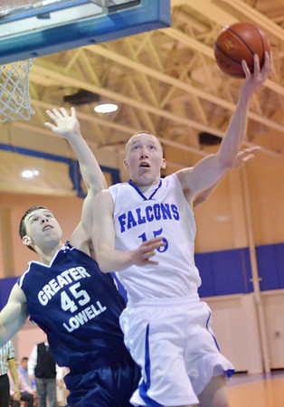 Danvers:  Danvers captain Sean Mahegan makes a off centered layup defended by Greater Lowell's Derek Ross.  photo by Mark Teiwes / Salem News