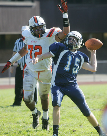 Peabody: Beverly's Ty Suggs, left, puts pressure on Peabody quarterback Jason Hiou. photo by Mark Teiwes / Salem News
