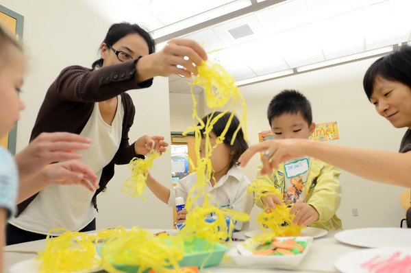 Hamilton: Aekyung Park, left, Mowon Yoon, 4, Shinhyeok Kim, 4, and Heesoun Kwon of all from Hamilton make a craft after reading books about pizza at the Hamilton-Wenham Public Library's Rhythm and Rhyme story time.  photo by Mark Teiwes /  Salem News
