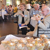 Danvers: As desert is served for the Peabody High School class of 1946 reunion, classmates Marilyn Fecteau and Charley Alexpulos, right, listen to a speach and jokes from Don Finegold at the Danversport Yacht Club.   photo by Mark Teiwes / Salem News