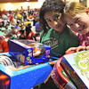 Salem: Yvonne Viqez, 11,  left and Kristen Butler, 10 received gifts at the Boys and Girls Club Christmas party including Littlest Pet Shop, and Hi Ho Cherry-O.  photo by Mark Teiwes  / Salem News