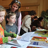 Salem:  Lucy, 8, left, Charlie, 6, and Mary Tuttle of Salem check out the books on auction at Salem Education Foundation spring fundraiser. photo by Mark Teiwes / Salem News