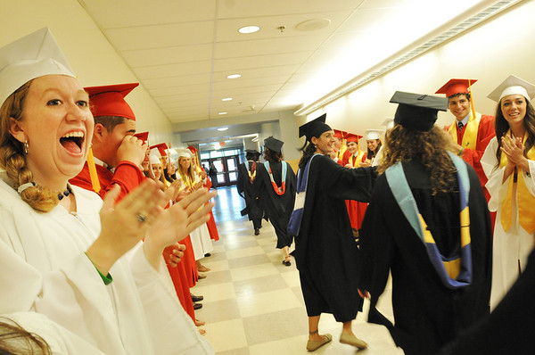Boxford: Evelyn Lebel, left, cheers for her teachers as they pass in the hall on the way to Masconomet's graduation. photo by Mark Teiwes / Salem News