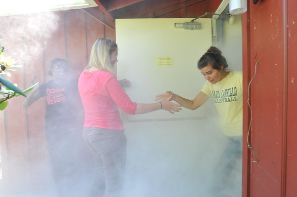Wenham:  Alanah Percy, left, Amelia Vierstra, and Sarah Riad, all Gordon College student resident advisors, emerge after crawling through a dorm filled with theatrical smoke to simulate fire conditions during a fire safety training.  photo by Mark Teiwes /  Salem News