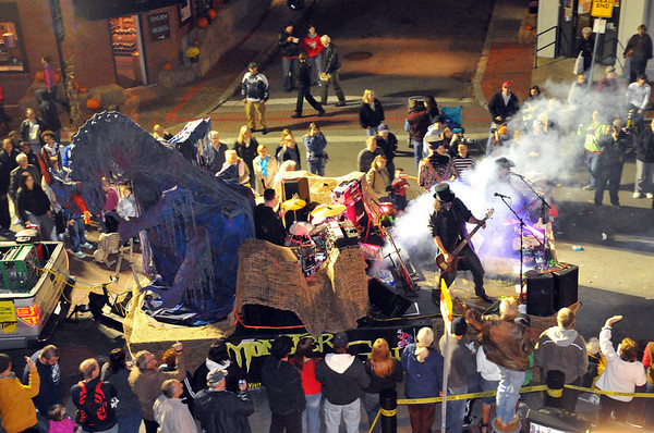 Salem:  A three piece rock band jams along Derby St. with the Monster Golf float. photo by Mark Teiwes / Salem News