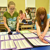 "Beverly:  Briscoe Middle School students Lorna Brennan, left, 13, and Nicole Shawn, 13, paste the names of people who died in the September 11 attacks, part of a ""wall of remembrance"" for Sept. 11, 2001.  The poster also includes personal thoughts from teachers, parents, and recollections from the 9/11 digital archive. photo by Mark Teiwes  / Salem News"