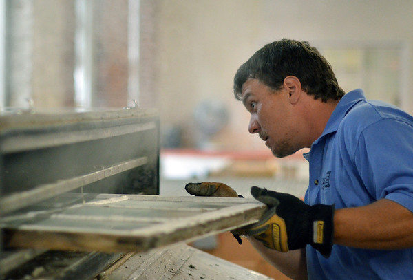 Peabody: Jason Merrill uses steam to remove glass to restore a old wooden window at the Window Woman workshop.  photo by Mark Teiwes / Salem News