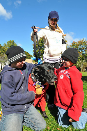 Beverly: Ethan Bagley, left, 12, Sherry Brindle and Aidan Lonergan, 7, all from Beverly, costumed their black lab mastiff Brewski as the wolf dressed as Red Riding Hood.  photo by Mark Teiwes / Salem News