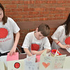 Salem: Zoe Poussard-Barham, 11, Freddie, 8, and Elodie Poussard, 8,  work on cards to send along with donations from a clothing drive for Japan.  photo by Mark Teiwes / Salem News