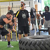 Danvers: Shawn Loiseau, All American linebacker at Merrimack College hits a tire with a sledge hammer watched by Pat Downey during a workout at Gridiron Training photo by Mark Teiwes /  Salem News