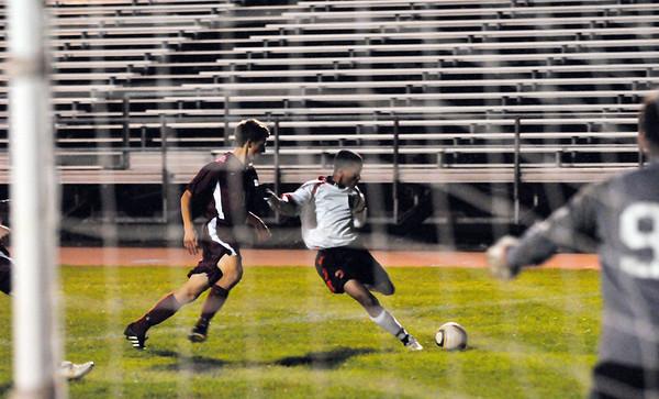 Salem:  Salem's Robert Abreu, center, takes aim for a shot on goal closely guarded by Gloucester's Sean Dixon. photo by Mark Teiwes / Salem News