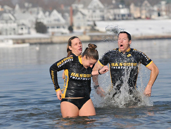 Salem:  Brandi Dion, left, Ashley Steeves, and Steve Dion all from Salem, react during a New Year's day ocean dip at Dead Horse Beach benefitting the Salem Food Pantry .    photo by Mark Teiwes  / Salem News