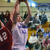 Danvers:  Danvers center George Merry, right, goes strong to the basket defended by Gloucester's David St. Peter.  photo by Mark Teiwes / Salem News