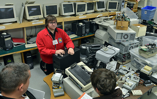 Middleton: North Shore Technical High School senior Dylan Baker speaks with a prospective student about the computer program which begins with hands on instruction with hardware repairs followed by software and network training.  photo by Mark Teiwes / Salem News