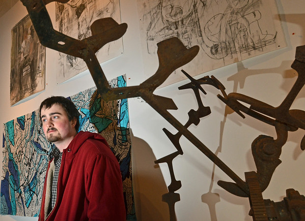"Beverly: Corey Luebbers stands in front of his painting ""Infinity Squared at the ""Art's Not Dead 2"" art show at 17 Cox Visual Art Center.   In the foregound is a sculpture by Roy Hawes entitled ""Cobbier Train""  photo by Mark Teiwes / Salem News"