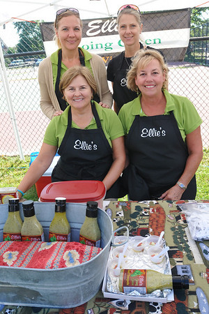 """Marblehead: Darnell Vipperman, left front, Ellie Monnin, Heidi Jarchow, left back, and Barbara Bane sell """"Ellie's Going Green Basil Vinaigrette"""" made at St. Andrew's Church during the Marblehead farmers market.   photo by Mark Teiwes / Salem News"""