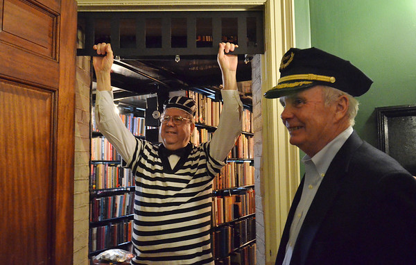"Salem: David Hart, left, was dealt a card saying, ""Do not pass go.  Go directly to jail.""  Luckily, his wife was dealt a ""Get out of jail free"" card.   Bob St. Pierre, right, former police chief, played the role of the jailer at the Salem Athenaeum's Monopoly themed party.  photo by Mark Teiwes"