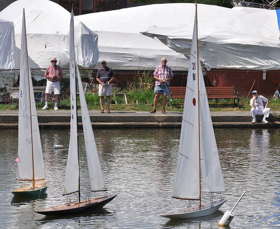 Marblehead: Ned Lakeman, left, John Skerry, and Biff Martin, Members of the Marblehead Yacht Club, race radio-controlled Cup Racers around Redds Pond.  Spectator Norman Card, right, came down to watch the race and is thinking about picking up the hobby.     photo by Mark Teiwes / Salem News