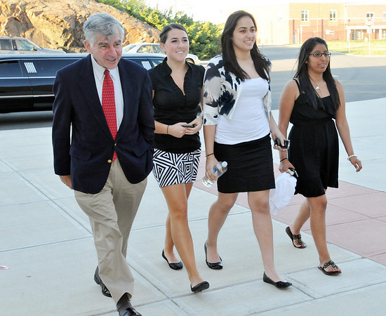 Salem: Former Massachusetts Gov. Michael Dukakis, left, walks into Salem High School accompanied by students Julia Pelletier, Radairy Peguero, and Fallon Fitzgerald, right.  The girls helped organize the 9th annual Service Learning Unity Celebration.   photo by Mark Teiwes / Salem News