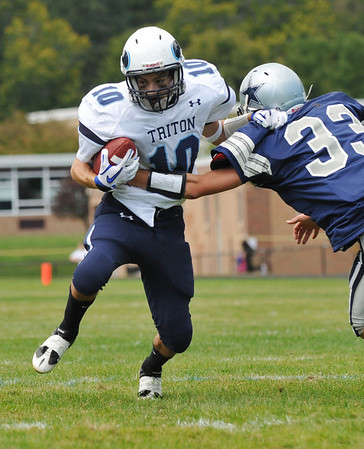 Hamilton: Triton High School varsity football player Matt Hill, left, makes a run gaining yardage as Hamilton-Wenham defenseman Alton Bynum attempts a tackle. photo by Mark Teiwes / Salem News