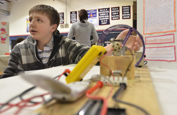 Middleton: North Shore Tech freshman Caleb Anderson explains how his  science fair electric battery project uses DC power to charge a cell phone battery and two triple a batteries.  photo by Mark Teiwes / Salem News