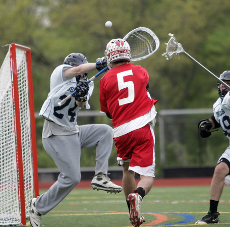 Wenham: Masco's Jack Hoesley, center, slides a shot past Hamilton-Wenham goalie Luke Drieze.  photo by Mark Teiwes / Salem News