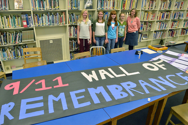 """Beverly:  Briscoe Middle School students Meredith Enright, left, Meaghan Rennick, Nicole Shawn, and Lorna Brennan create a """"wall of remembrance"""" for Sept. 11, 2001 with help from librarian Alexandra Woznick, right.  photo by Mark Teiwes  / Salem News"""