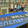 "Beverly:  Briscoe Middle School students Meredith Enright, left, Meaghan Rennick, Nicole Shawn, and Lorna Brennan create a ""wall of remembrance"" for Sept. 11, 2001 with help from librarian Alexandra Woznick, right.  photo by Mark Teiwes  / Salem News"