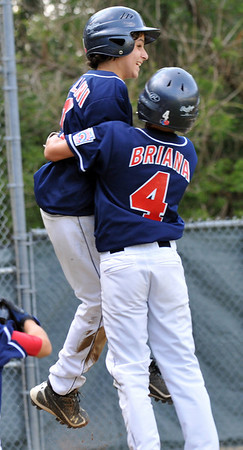 Beverly: Peabody West player Traverse Briana, right, bear hugs and lifts up John Villani after he came home to score the game winning run.   Mark Teiwes / Salem News