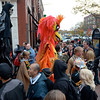 Salem: Two costumed people soar above the crowd as they come out onto Washington Street.  photo by Mark Teiwes / Salem News