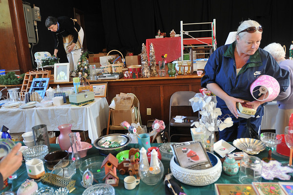 Salem: Cynthia Cecelski, left, puts out items for purchase as Andea Foss looks for interesting items to buy at a fall festival raising money for the Immaculate Conception Parish. photo by Mark Teiwes  / Salem News
