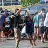 Danvers: Danvers High School Band members Dan DeLucia, left and Jillian Enos have a water fight during a fundraiser car wash in the Firestone Tire and Service parking lot.     photo by Mark Teiwes / Salem News