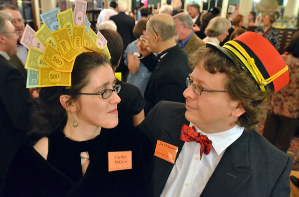 Salem:  Carolyn McGuire wears a Monopoly money headdress, and her husband Joe is dressed as train conductor for the the Salem Athenaeum's Monopoly themed party.   photo by Mark Teiwes
