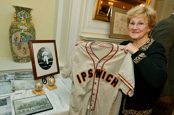 Ipswich: Cathy Mackey-Carter holds a historic jersey around other baseball memoriabilia at the Ipswich High School athletic hall of fame ceremony as class of '41 baseball player Ed Mackey was inducted. photo by Mark Teiwes / Salem News