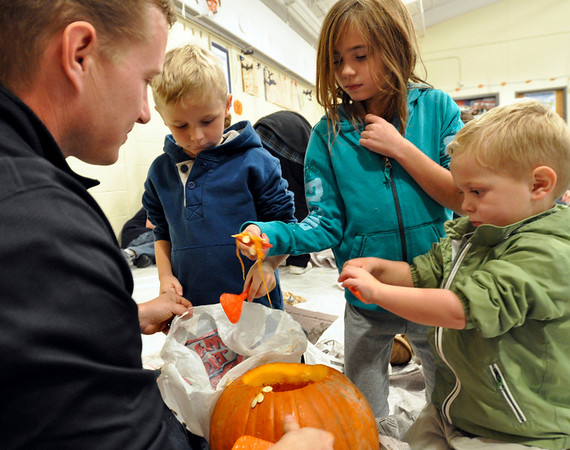 Middleton: Peter Richardson, left, watches as his kids Matthew, 5, Paige, 7, and Ryan, 3, scoop out the seeds from a pumpkin.   photo by Mark Teiwes / Salem News