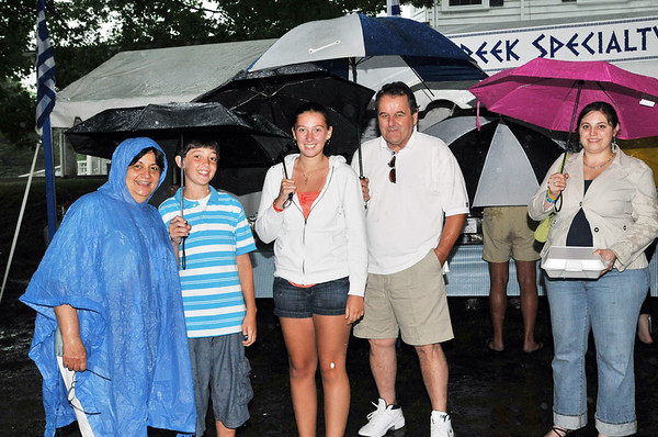Ipswich: Features gatherings -- Greek festival & clambake.  Janet Squires, left, of Georgetown, Peter Pappas, of Ipswich, Dakota Pappas, of Ipswich, Jim Squires of Georgetown, and Joanna Scaparotti of Byfield all came ready for the rain.  photo by Mark Teiwes / Salem News