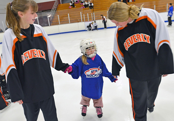 Gloucester:  Beverly/Danvers varsity girls hockey players Allison Houde of Danvers, left, and Emily Ouellette of Danvers skate with 4-year-old Lauren Caley of Beverly.  photo by Mark Teiwes  / Salem News