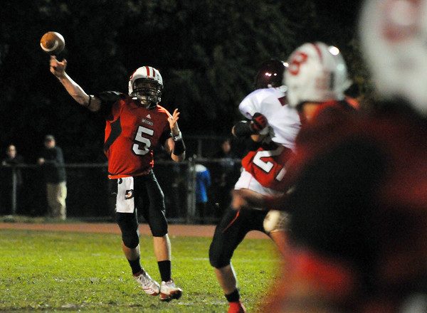 Salem: Salem quarterback Brad Skeffington, left, releases a pass during last night's game against Gloucester .  photo by Mark Teiwes / Salem News