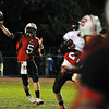 Salem: Salem quarterback Brad Skeffington, left, releases a pass during last night's game against Gloucester .  photo by Mark Teiwes / Salem News