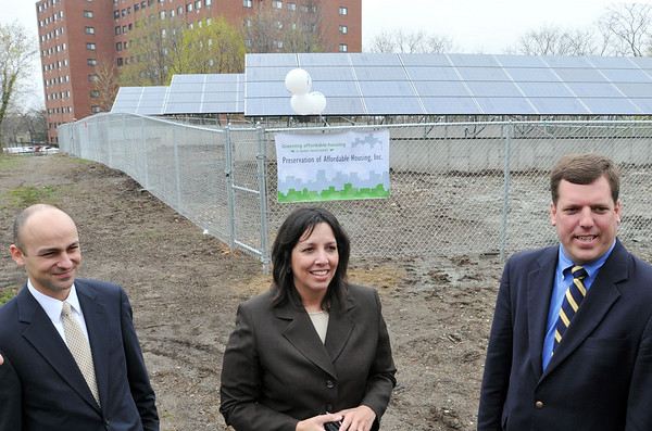 Salem:  Toby Ast, left, of Preservation of Affordable Housing Inc, Mayor Kim Driscoll, and Andy Brydges of Massachusetts Clean Energy Center stand before recently installed solar panels outside the Fairweather Apartments.  photo by Mark Teiwes