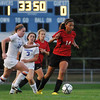 Danvers:  Salem High School girls soccer player Alix Bryant dribbles the ball upfield with Danvers player Becky Landers close behind.  photo by Mark Teiwes / Salem News