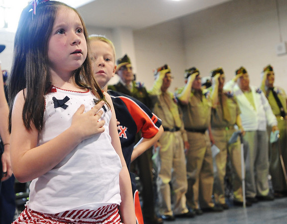 Danvers: Kindergartner Emma Hatch pledges allegiance to the flag with veterans saluting behind her during a patriotic school assembly at Great Oak School. photo by Mark Teiwes / Salem News