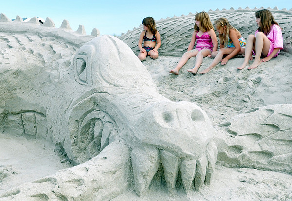 "Ipswich: Angelina Squillante, 5, left, Ashely Moore, 9, Amanda Kaskeski, 9, and Brianna Shea, 9, hang out in a sand sculpture entitled ""Dragon Snacks"" after the Sand Blast contest.   photo by Mark Teiwes / Salem News"
