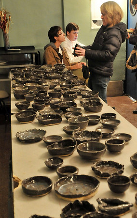 Danvers: St. John's Prep sophomores David Bradburn, left, and Tim Vincent take donations at the Empty Bowls Dinner Party.   Marylou Lemieux, right, checks out bowls that were made by St. John's Prep students, family and friends   All proceeds benefit Haven From Hunger.  photo by Mark Teiwes  / Salem News