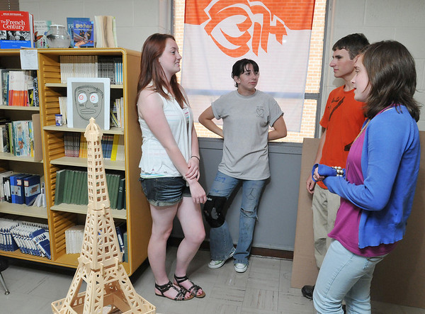 Danvers: Deirdre Moriarty, left, Jacqui Sweeney, Tanner Henry, and Ryan Gibbons, right, reminisce about their trip last April to France.  The flag behind them is from the French department of Vendee. Photo by MARK TEIWES
