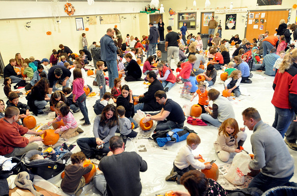 Middleton: The cafeteria at the Fuller Meadow School was transformed into a pumpkin carving workshop with the floors covered in plastic.   photo by Mark Teiwes / Salem News