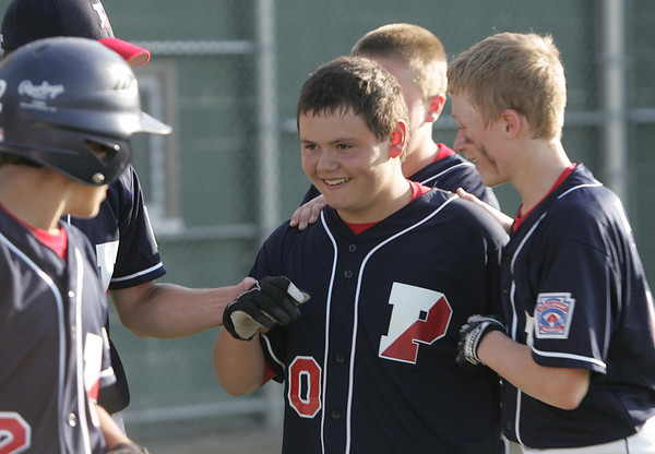 Lynn: Peabody West teammates congratulate Marc Ginetti, center, for hitting a home run against Salem American in a District 16 little league game.  photo by Mark Teiwes / Salem News