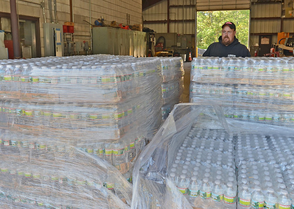 Wenham: Sean Reed, Wenham DPW mechanic, stands with a supply of bottled water for Wenham residents after E. coli was found in the public water supply. Water will also be available 9 a.m. to 1 p.m. on Saturday at 91 Grapevine Rd.   photo by Mark Teiwes / Salem News